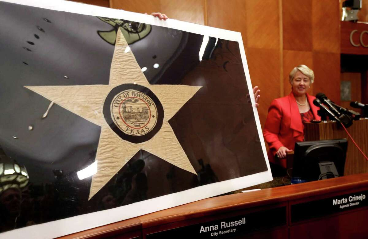 Mayor Annise Parker displays a 1915 prototype for the Houston flag. Preservation Houston helped raise cash to restore it.