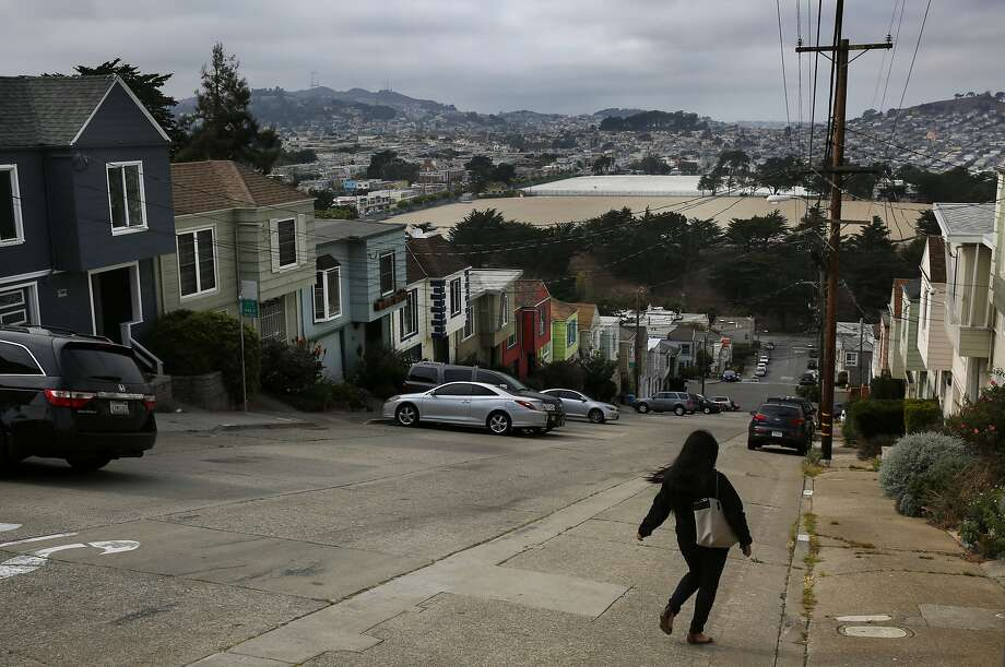 A woman strolls down a hill in view of the University Mound Reservoir, which is one of the reservoirs where San Francisco stores water in various neighborhoods. This one is in the Portola district. Photo: Leah Millis, The Chronicle
