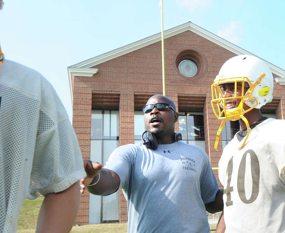 Brunswick School football coach Jarrett Shine, center, instructs his players during practice at the school in Greenwich, Conn., Wednesday, Sept. 9, 2015.