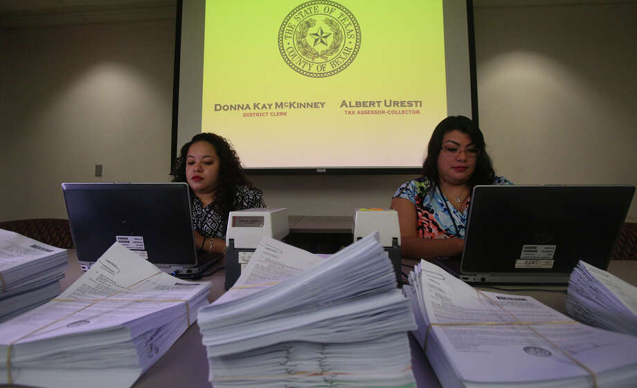 Nikki J. Garcia (left) and Roxanne H. Mujica of the Bexar County district clerk's office work on laptops Wednesday September 9, 2015 in front of stacks of citations (foreground) that will be dissiminated to delinquent taxpayers to notify them that they are being sued for unpaid taxes. Despite written notices, some property owners have still not paid their taxes so a legal firm has been hired to collect the taxes on behalf of Bexar County, the city of San Antonio, a multitude of school districts and many surrounding cities and entities. Bexar County District Clerk Donna Kay McKinney urged delinquent taxpayers at a press conference to contact the Bexar County Tax Office to learn more about monthly payment options. Photo: John Davenport /San Antonio Express-News / ©San Antonio Express-News/John Davenport
