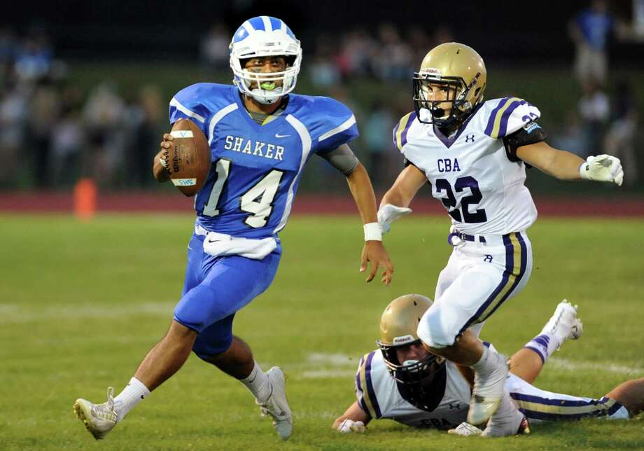 Shaker's quarterback Wahid Nabi, left, looks to pass as CBA's Nick DeNicola defends during their football game on Friday, Sept. 4, 2015, Shaker High in Latham, N.Y. (Cindy Schultz / Times Union) Photo: Cindy Schultz / 00033230A