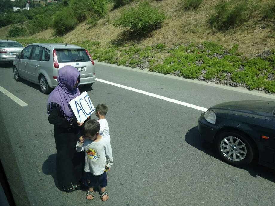 "A Syrian refugee woman with her two young boys begs for money in the middle of Istanbul's main highway on Aug. 19. She holds a sign, ""Aciz,"" that means helpless or hungry in Turkish. (Paul Grondahl / Times Union)"