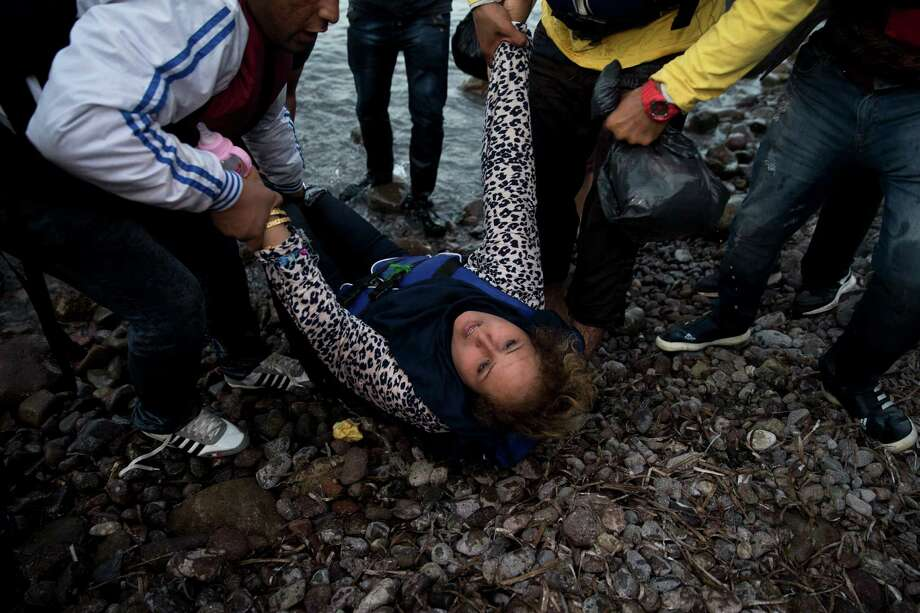 An Afghan woman collapses after she arrived with others on a dinghy at Lesbos island, Greece, Wednesday, Sept. 9, 2015. The head of the European Union's executive says 22 of the member states should be forced to accept another 120,000 people in need of international protection who have come toward the continent at high risk through Greece, Italy and Hungary. (AP Photo/Petros Giannakouris) ORG XMIT: XPG144 Photo: Petros Giannakouris / AP