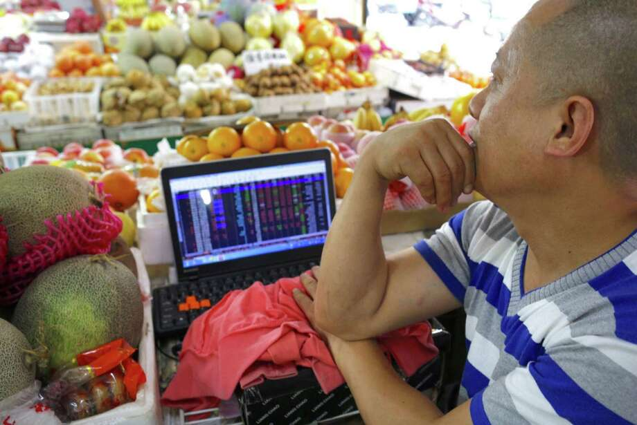 A fruit vendor checks stock prices on his computer while waiting for customers in a market in eastern China on Wednesday. Chinese authorities have imposed a range of extraordinary restrictions on the sale of stocks. Photo: STR / CHINATOPIX