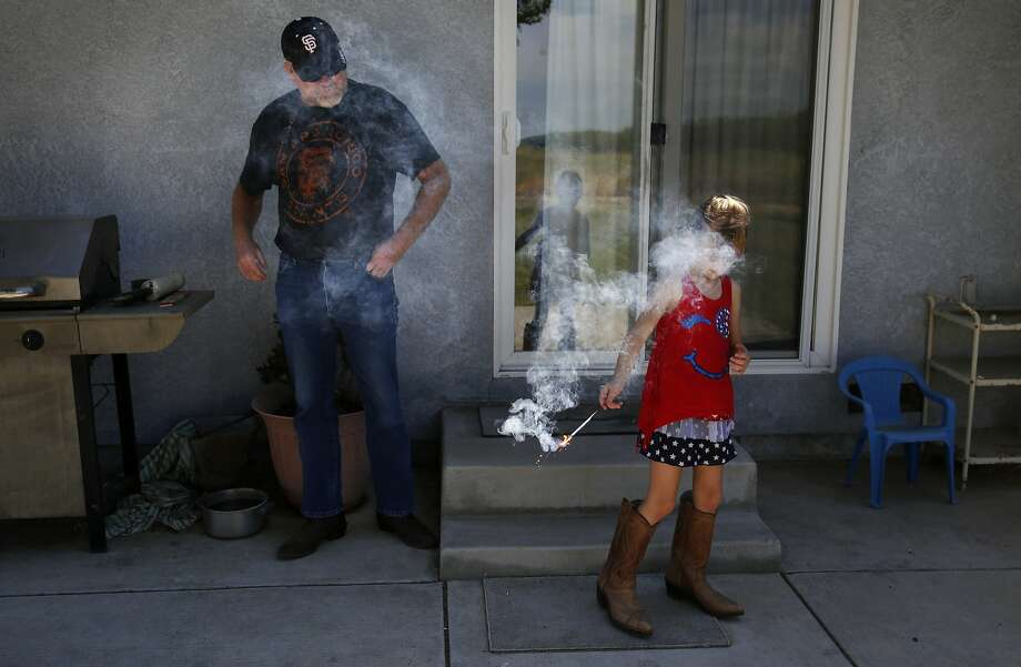 Kaylie Baker, 6, plays with a sparkler as grandfather Dennis Baker, 53, supervises her at his home. With cuts to his water supply, he can't harvest a third cut of hay this year. Photo: Leah Millis, The Chronicle