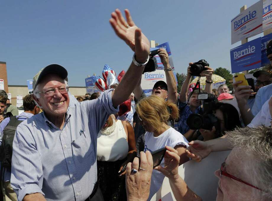 Democratic presidential candidate Sen. Bernie Sanders, I-Vt, is swarmed by supporters as he arrives to march in the  Labor Day parade Monday, Sept. 7, 2015, in Milford, N.H. (AP Photo/Jim Cole) Photo: Jim Cole / Associated Press / AP