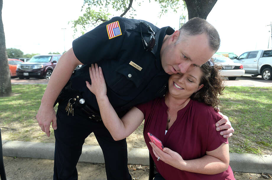 """Alicia Smith gets a hug from Mitch Hanley, a fellow officer and step-brother of her husband Jared """"Ty"""" Smith at the memorial fundraiser in honor of Officer Smith, who passed away last week following a two-year battle with leukemia. Area businesses sent in large pre-orders for the links and boudin meals, and a steady stream of walk-up traffic quickly filled the lot behind the Beaumont Police station downtown. The proceeds of the event will go toward assisting his wife Alicia Smith with medical costs.  Photo taken Tuesday, September 8, 2015  Photo by Kim Brent / Beaumont Enterprise"""