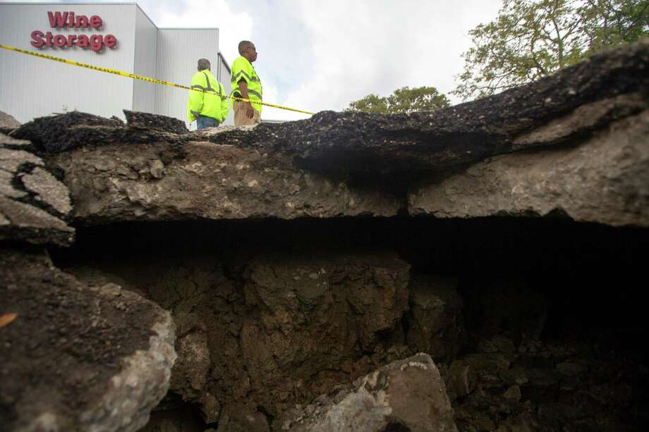 City of Houston employees, Chris Broussard, left, and Roderick James survey an area after a truck fell into a sink hole in the 2200 block of Calumet near the South Freeway, Thursday, Sept. 10, 2015, in Houston. Nicole Jones said she was driving when the street collapsed beneath her and the right front wheel dropped into the deep hole. Jones said she tried to back up, but the pickup would not budge and a wrecker pulled the truck from the hole. Photo: Cody Duty, Houston Chronicle / © 2015 Houston Chronicle