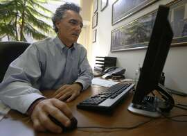 Thomas Dart, sheriff of Cook County, Ill., looks at computer screen in an office at his Chicago headquarters on Thursday, July 23, 2015. For years, Dart has been taking aim at Backpage.com, a classified ad website with an adult services section that has been shown in court to be used by sex traffickers - some who've sold minors for sex. (AP Photo/Martha Irvine)
