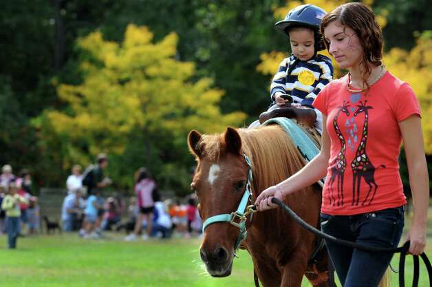 Volunteer Tori Brannigan, 17, right, leads Edgar Monroy, 2, of Albany on a pony ride during Harvest Fest on Sunday, Sept. 26, 2010, at the Crossings in Colonie, N.Y. (Cindy Schultz / Times Union) ORG XMIT: MER2015090817355814 Photo: Cindy Schultz / 00010360A