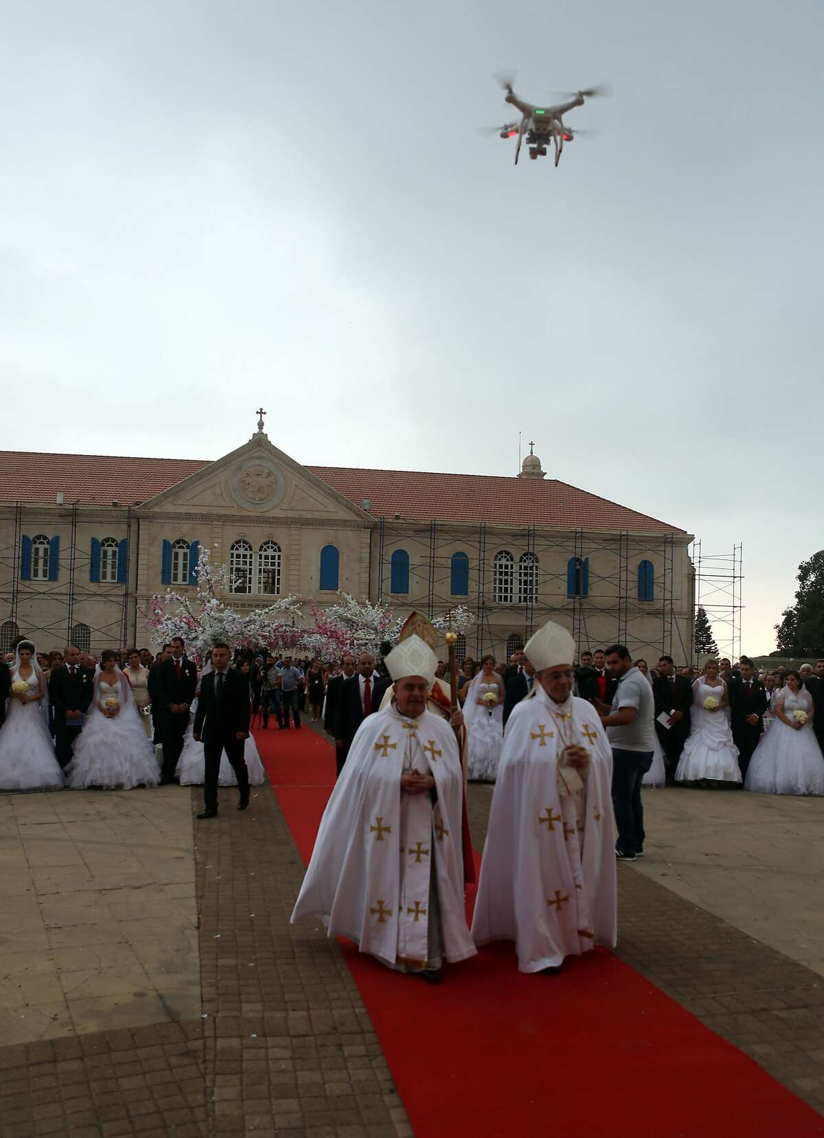 A drone flies over Lebanese Maronite Christian priests and couples taking part in a mass wedding at the Maronite Patriarchate in Bkerke on September 6, 2015. Thirty-seven couple got married during the event organised by the Maronite league. AFP PHOTO / PATRICK BAZPATRICK BAZ/AFP/Getty Images