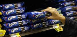 FILE - In this Feb. 9, 2011, file photo, a shopper selects Oreo cookies at a Ralphs Fresh Fare supermarket in Los Angeles. Activist investor Bill Ackman is paying approximately $5.5 billion for a 7.5 percent stake in Mondelez International Inc., the maker of products, including Oreo cookies, according to reports, Thursday, Aug. 6, 2015.  (AP Photo/File)