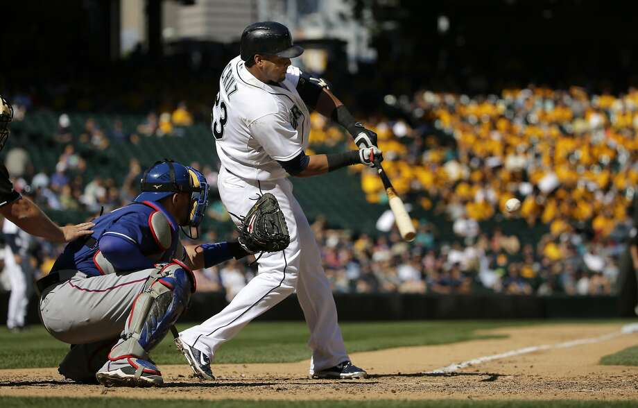 Seattle Mariners' Nelson Cruz, right, hits a two-run home run in the seventh inning of a baseball game as Texas Rangers catcher Bobby Wilson looks on, Thursday, Sept. 10, 2015, in Seattle. The Mariners won 5-0. (AP Photo/Ted S. Warren) Photo: Ted S. Warren, Associated Press