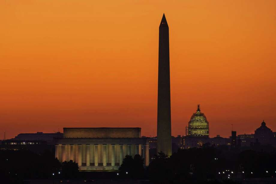 The orange sky of sunrise is captured behind the skyline of Washington, Tuesday, Sept. 8, 2015, on the first day back to work for the U.S. Congress after their summer recess. (AP Photo/J. David Ake) Photo: J. David Ake, STF / AP