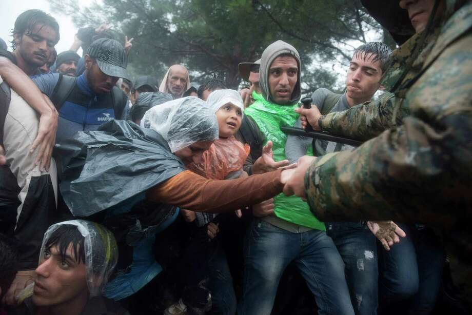 Macedonian border police help refugees and migrants in heavy rainfall pass from the Greek village Idomeni to Macedonia on Thursday. Greek authorities registered about 17,000 people on the island of Lesbos in a few days. Photo: Giannis Papanikos, STR / AP