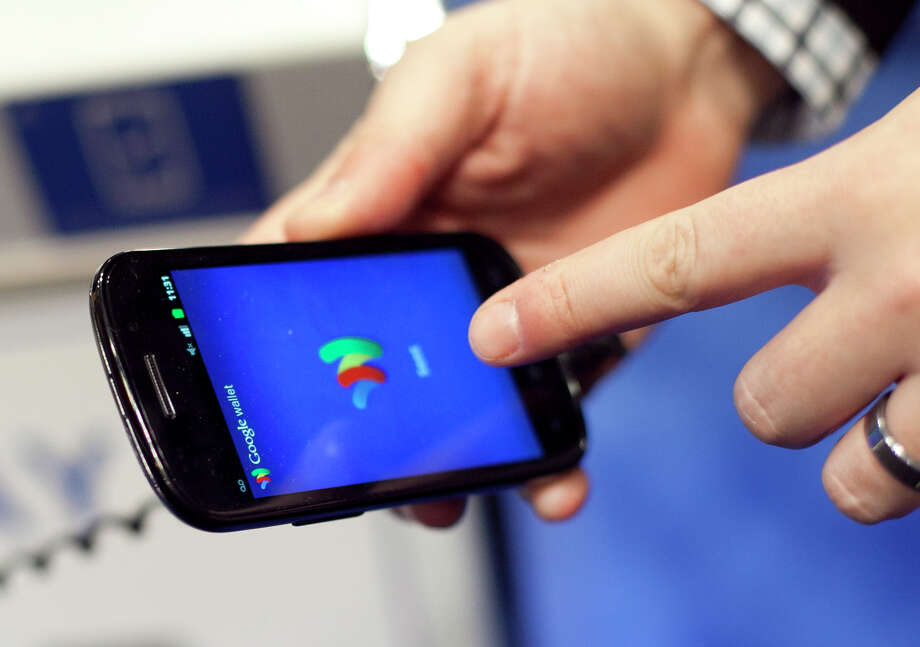 FILE - In this Jan. 17, 2012 file photo, a person tries a smartphone loaded with Google Wallet at the National Retail Federation in New York.  Google's answer to the Apple Pay mobile-payment service is debuting in the U.S., marking a do-over by the company behind the world's most-used operating system for smartphones. Android Pay will be similar to Apple Pay, except it works on Android phones rather than Apple's iPhones.   Google Wallet, the company's first attempt in mobile payments, flopped because it didn't have a big enough network of compatible devices and wireless carriers willing to work with it.   (AP Photo/Mark Lennihan) ORG XMIT: NY113 Photo: Mark Lennihan / AP