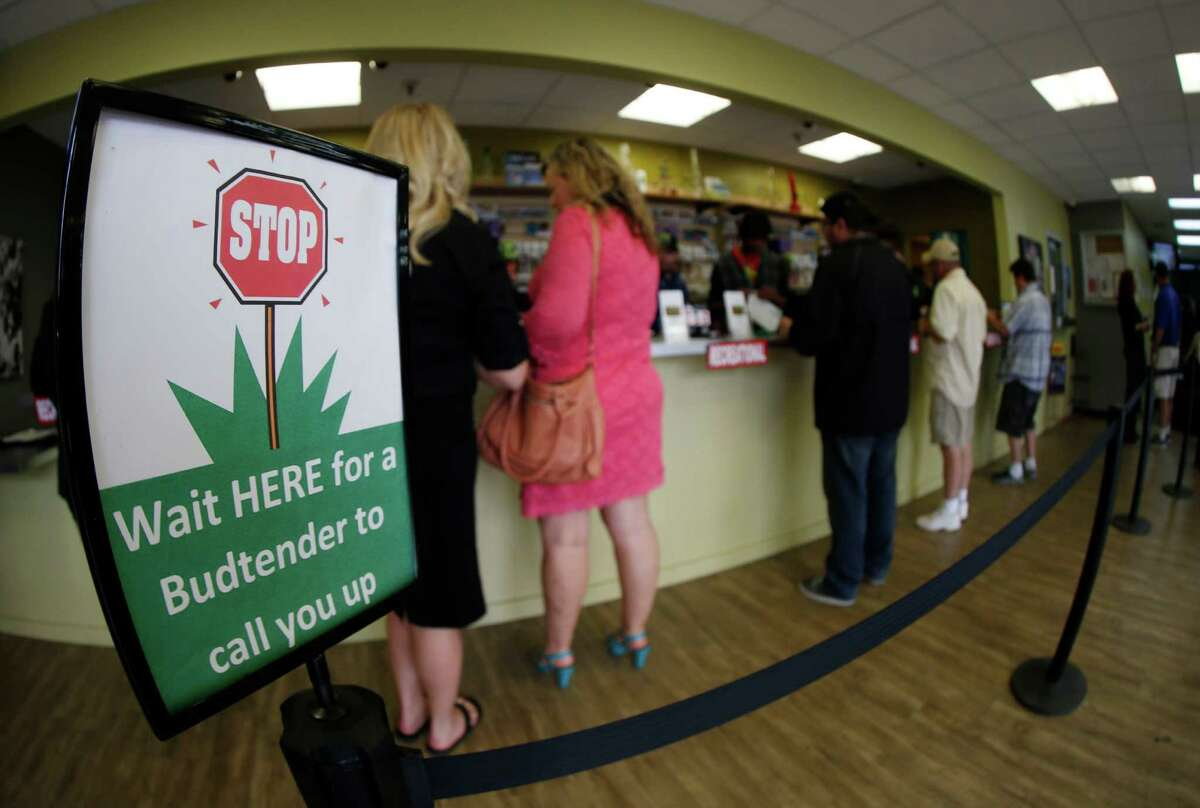 In this photograph taken with a fisheye lens Saturday, April 25, 2015, buyers make their purchases at a medical marijuana dispensary in Colorado. (AP Photo/David Zalubowski)