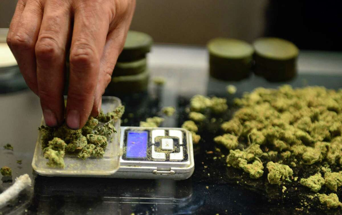 (FILES) In this July 4, 2014 file photo, a vendor weighs buds for card-carrying medical marijuana patients attending Los Angeles' first-ever cannabis farmer's market at the West Coast Collective medical marijuana dispensary, in Los Angeles, California. (Frederic J. Brown/AFP/Getty Images)
