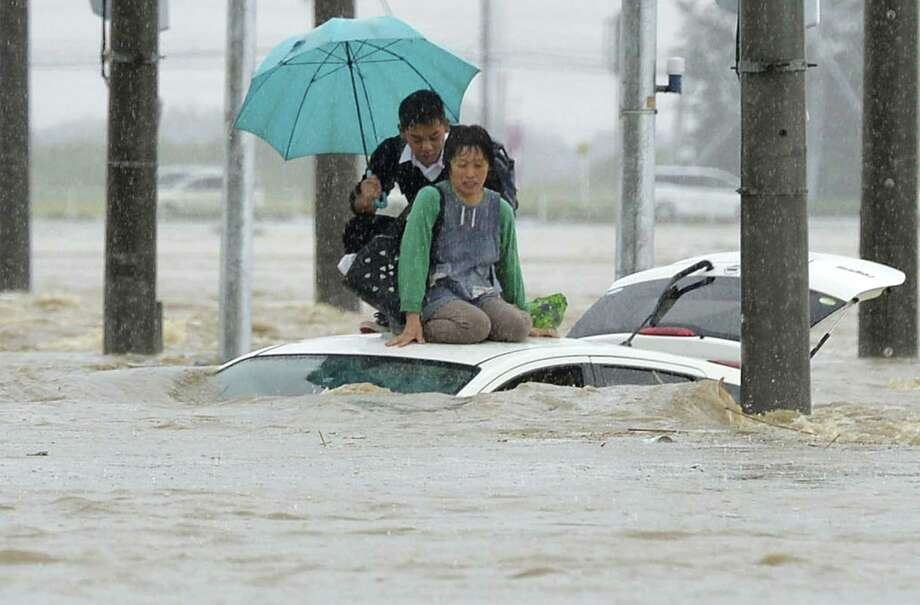 People wait for help as their vehicle becomes submerged in flooding near Tokyo on Thursday. Heavy rains pummeled Japan for a second straight day, overflowing rivers and causing landslides. Photo: Aé‰â€œ(degrees)'q O, SUB / Kyodo News