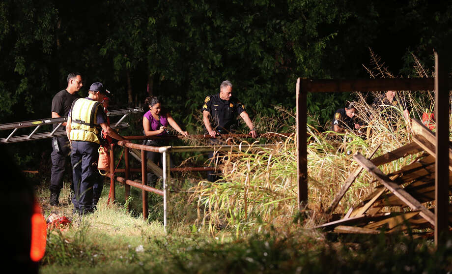 Rescue crews retrieve a drowning victim's body from a culvert  near Barbara Drive and McCullough on  September 10, 2015. Photo: Tom Reel, San Antonio Express-News