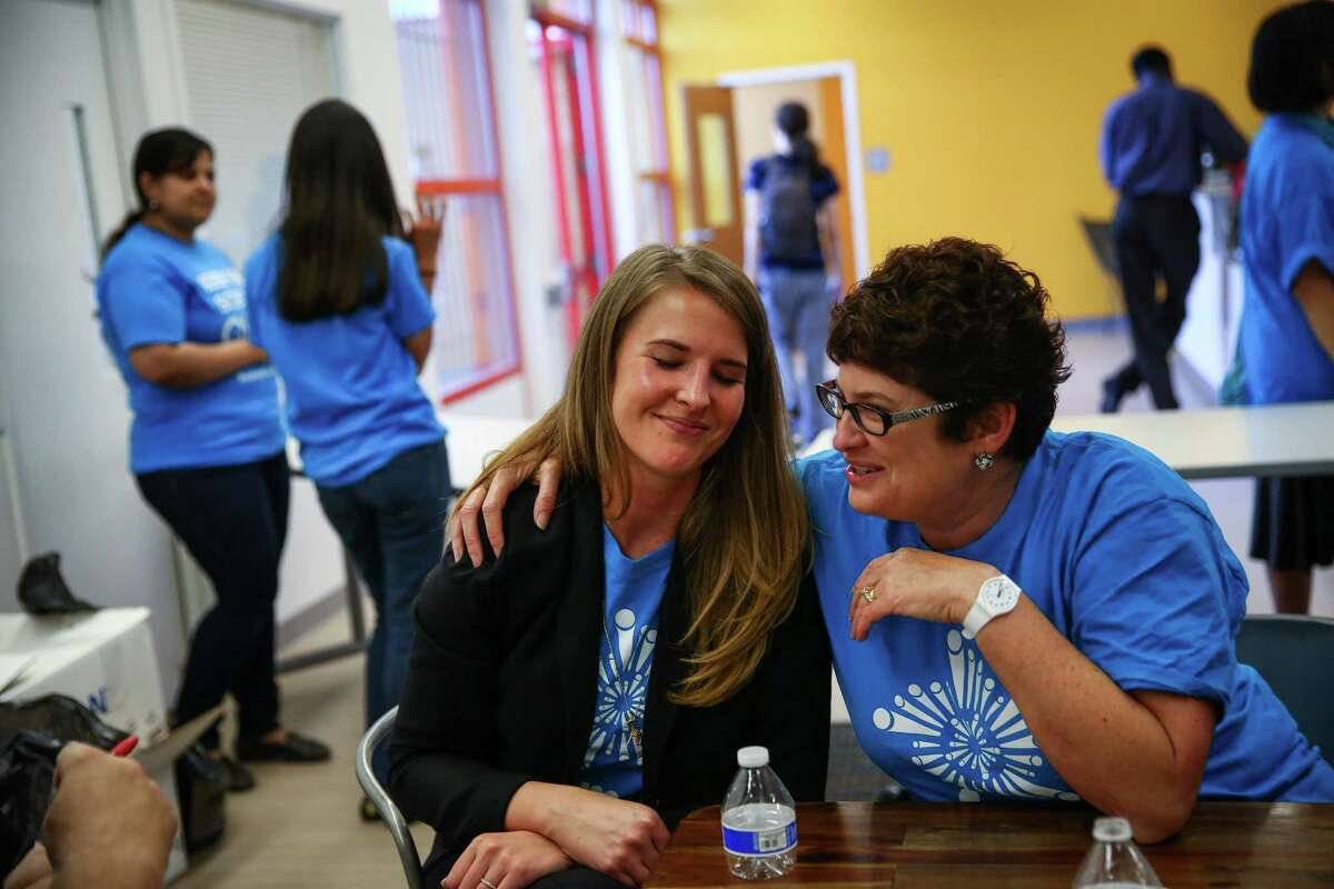 Principal Malia Burns, executive director of Summit Sierra public charter school, is hugged by parent Lynn Gilliland after a rally to support the schools and to call for Governor Jay Inlsee and the legislature to show their support. Photographed on Thursday, September 10, 2015.