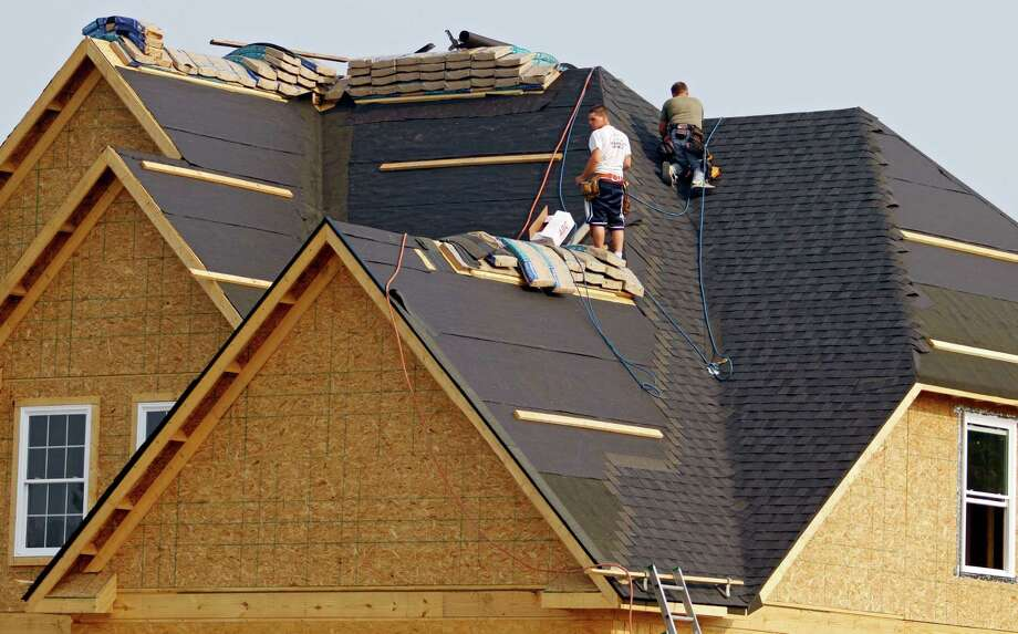 In this Friday, May 25, 2012, file photo, roofers shingle a new home under construction in Columbia Station, Ohio Friday, May 25, 2012. Americans bought new homes in May at the fastest pace in more than two years. The increase suggests a modest recovery in the housing market continues, despite weaker job growth. The Commerce Department says that sales of new homes increased 7.6 percent in May from April to a seasonally adjusted annual rate of 369,000 homes. (AP Photo/Mark Duncan) Photo: Mark Duncan, STF / 2011 Assocated Press