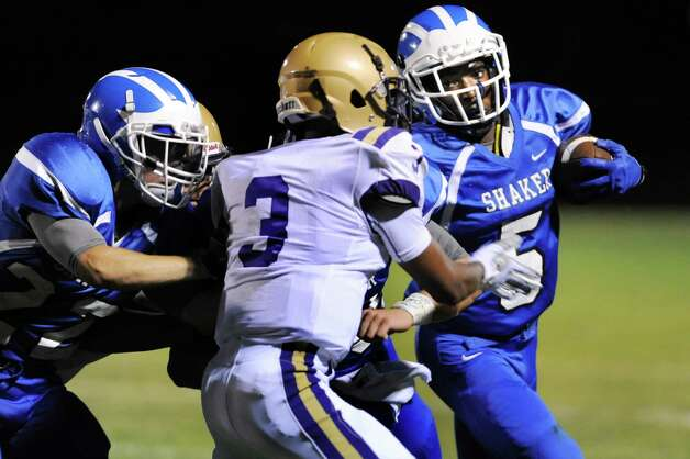Shaker's Ronel Forde, right, carries the ball as CBA's Amir Taylor defends during their football game on Friday, Sept. 4, 2015, Shaker High in Latham, N.Y. (Cindy Schultz / Times Union) Photo: Cindy Schultz / 00033230A