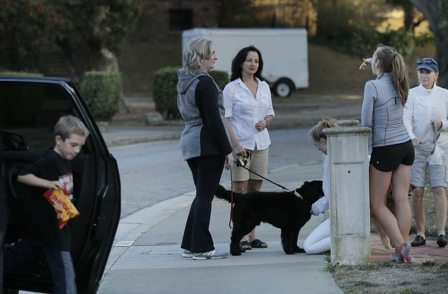 Mary Paglieri, a coyote expert for the Little Blue Society, center (white shirt) talks with neighbors as she investigates reports of a pack of coyotes scaring residents of the Ingleside Terraces neighborhood in San Francisco, Cali., on Thursday, September 10, 2015.  Photo: Carlos Avila Gonzalez, The Chronicle