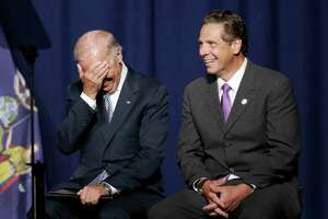 Vice President Joe Biden covers his face with his hand and New York Gov. Andrew Cuomo laughs as a speaker makes a comment about Republican presidential candidate Donald Trump, Thursday, Sept. 10, 2015, at a labor rally in New York. (AP Photo/Mark Lennihan) ORG XMIT: NYML102