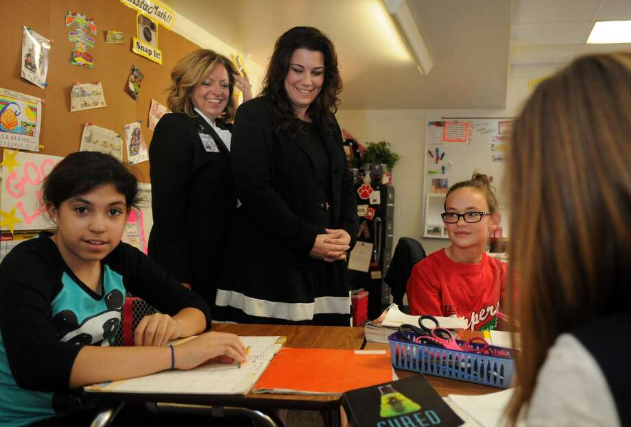 Jessica Frost, center, a principal partner at Tomball Intermediate School and Principal Crystal Romero-Mueller, standing at left, chat with sixth-graders Kylle Huey, right, and Rhianna McLendon, left, during a classroom visit last year. Photo: Jerry Baker, Freelance