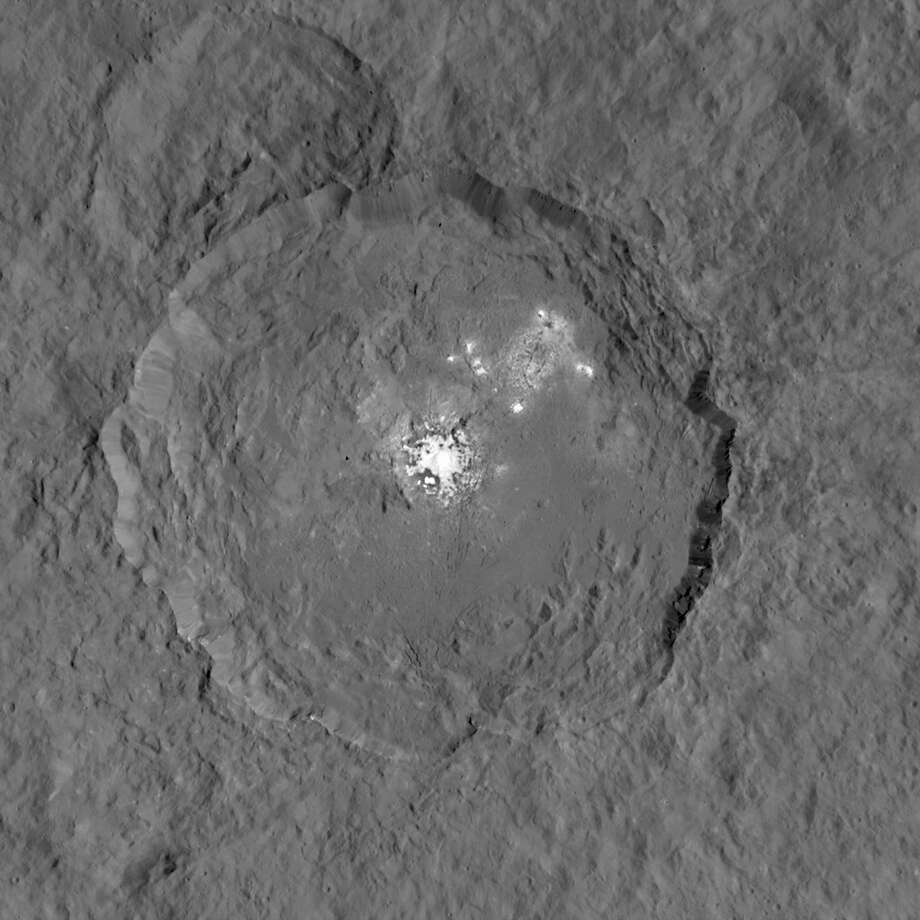 This photo, taken by NASA's Dawn Spacecraft from 915 miles about the dwarf planet Ceres, provides the greatest detail yet of the mysterious glowing spots. They were first detected by the Hubble Space telescope in 2004 and have baffled scientists ever since.  Photo: NASA