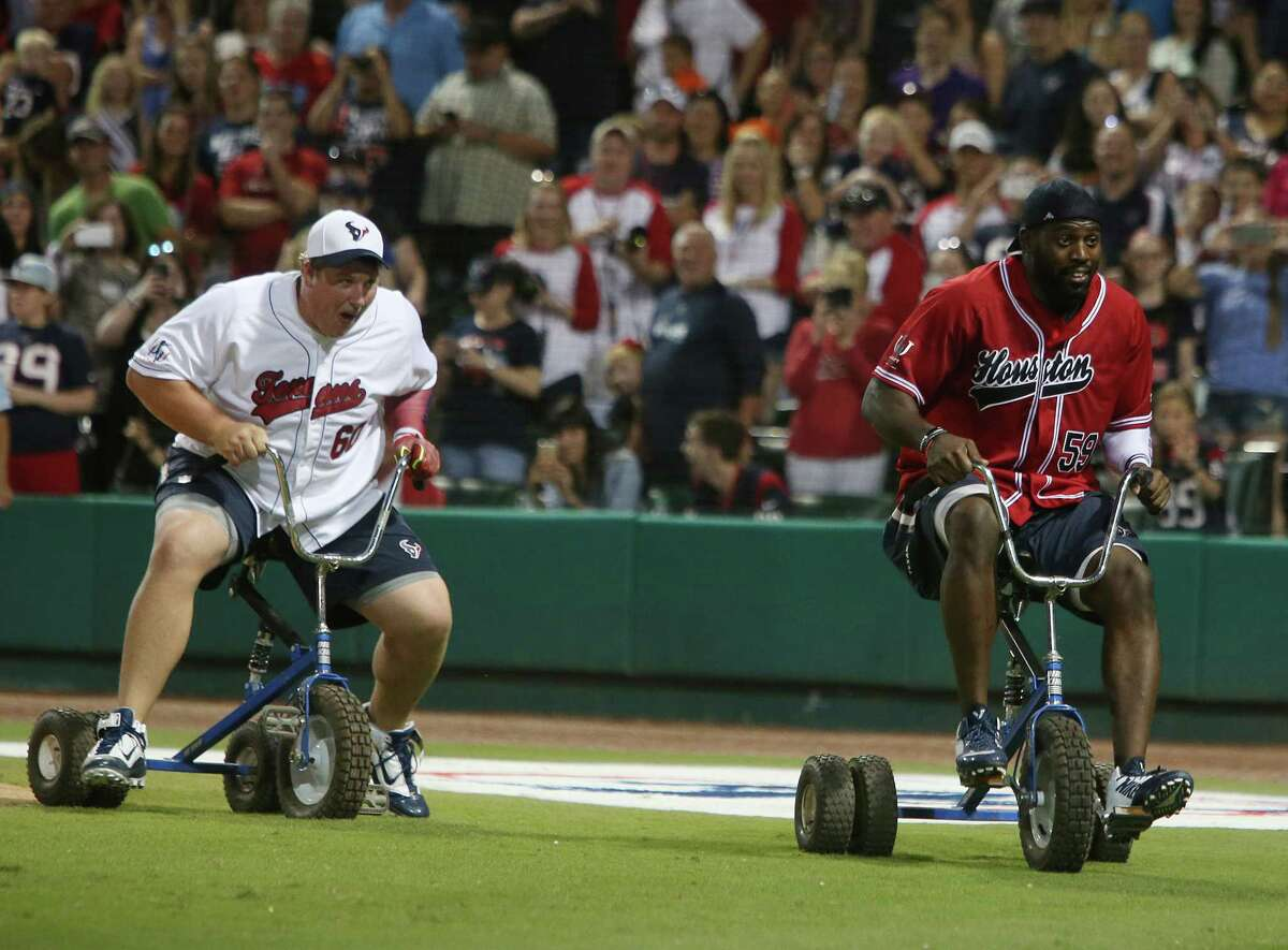 Offense Ben Jones and Defense Whitney Mercilus race for the finish line during a tricycle race in between innings during the J.J. Watt Charity Classic at Constellation Field on Friday, May 1, 2015, in Sugar Land. ( Mayra Beltran / Houston Chronicle )