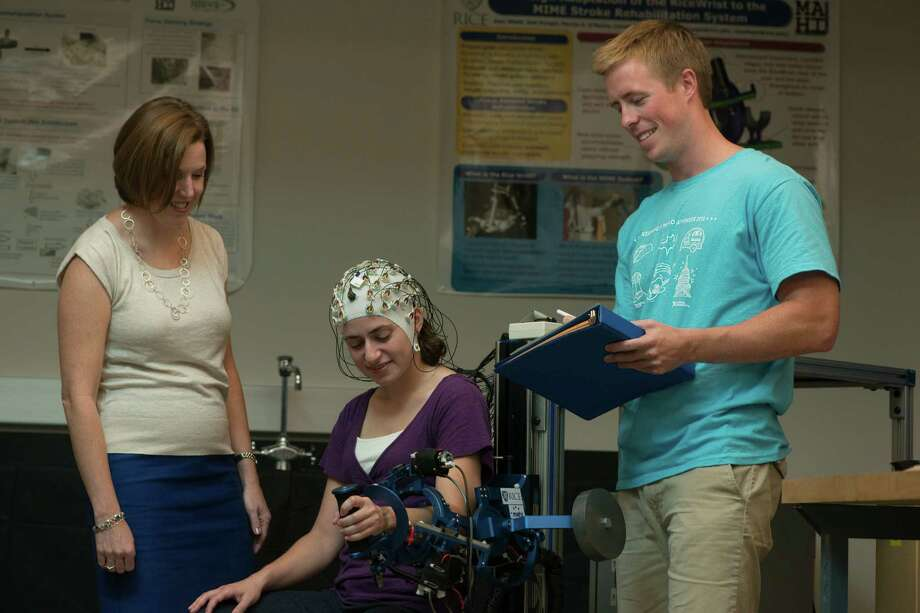 Marcia O'Malley, professor of mechanical engineering and of computer science at Rice University, stands with former postdoctoral research associate Amy Blank and former graduate student James French, with the MAHI Exo-II, an arm exoskeleton developed at Rive University's Mechatronics and Haptic Interfaces Lab. The cap worn on Blank's head is intended to be used to detect the user's intent (via EEG) to move their arm.