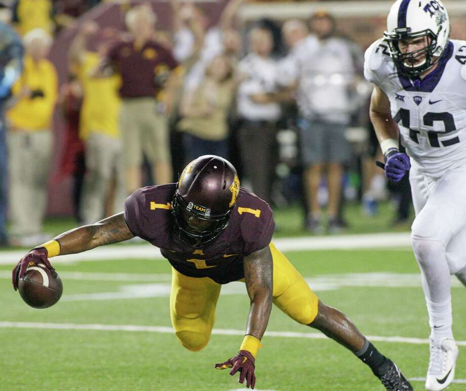 Minnesota wide receiver KJ Maye (1) stretches the ball across the goal line for a second-half touchdown as he is pursued by TCU linebacker Ty Summers (42) during an NCAA college football game Thursday, Sept. 3, 2015, in Minneapolis. TCU won 23-17. Photo: Paul Battaglia /Associated Press / FR1768 AP