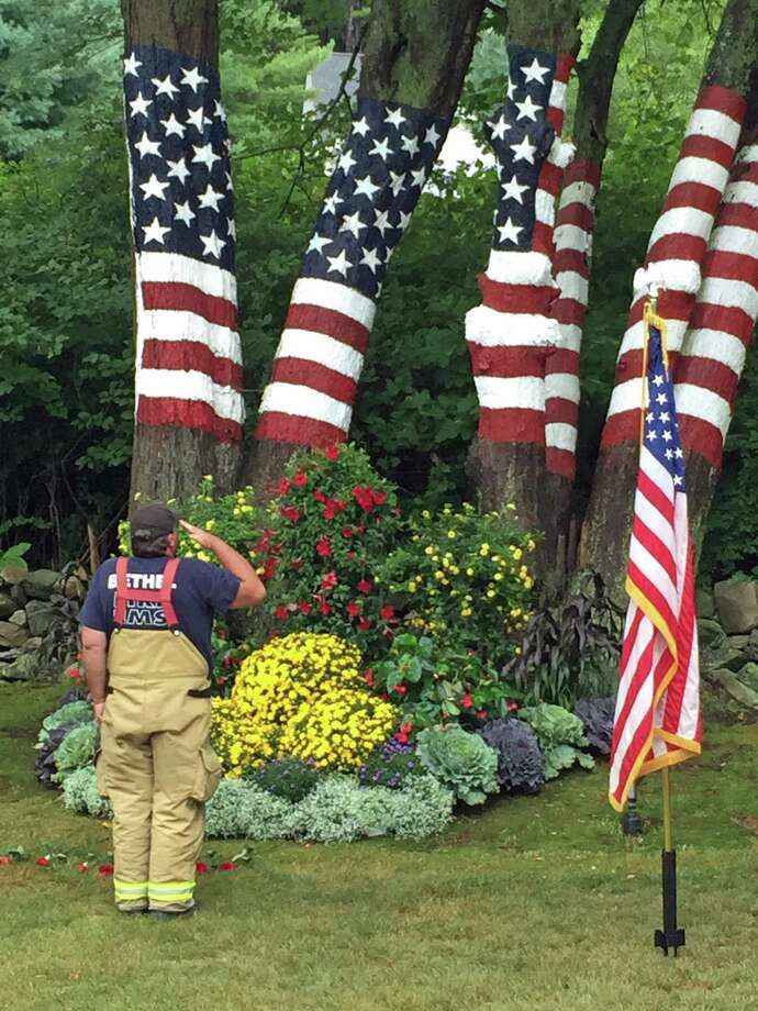 A Bethel firefighter salutes the American flag painted across six maple trees Friday during a 9/11 memorial service at the Newtown home of Howard and Jeanette Lasher. Photo: Brian Koonz / Hearst Connecticut Media / Connecticut Post