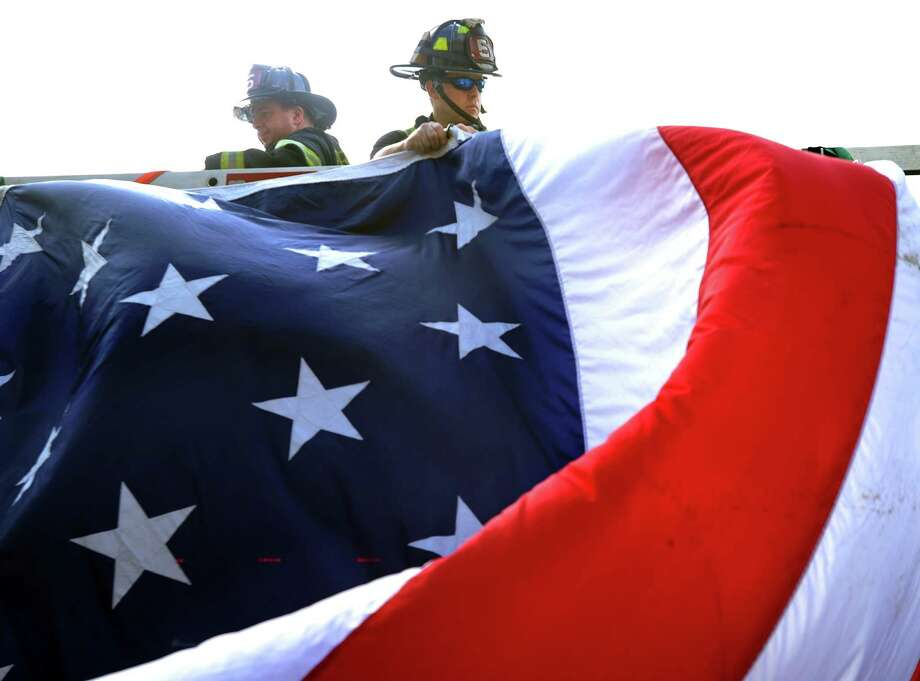 Firefighters Charles McNeiece III, left, and Terry Mincy stand on Ladder Five as they begin to take down the American Flag Friday, Sept. 11, 2015, at the Bridgeport Fire Department following a remembrance ceremony honoring the victims of the attacks on the United States on September 11, 2001. Photo: Autumn Driscoll / Hearst Connecticut Media / Connecticut Post