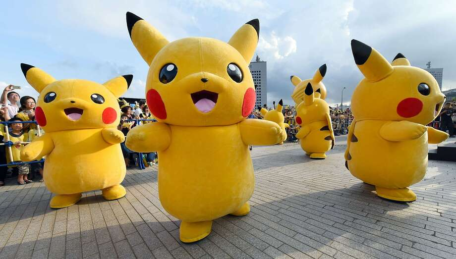 """Dozens of people dressed up as Pikachu, the famous character of Nintendo's videogame software Pokemon, dance with fans as the final of a nine-day """"Pikachu Outbreak"""" event takes place to attract summer vacationers in Yokohama, in suburban Tokyo, on August 16, 2015.       AFP PHOTO / Toru YAMANAKATORU YAMANAKA/AFP/Getty Images Photo: Toru Yamanaka, AFP / Getty Images"""
