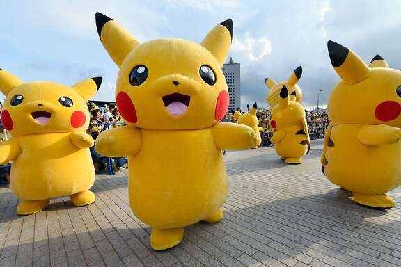 "Dozens of people dressed up as Pikachu, the famous character of Nintendo's videogame software Pokemon, dance with fans as the final of a nine-day ""Pikachu Outbreak"" event takes place to attract summer vacationers in Yokohama, in suburban Tokyo, on August 16, 2015.       AFP PHOTO / Toru YAMANAKATORU YAMANAKA/AFP/Getty Images"