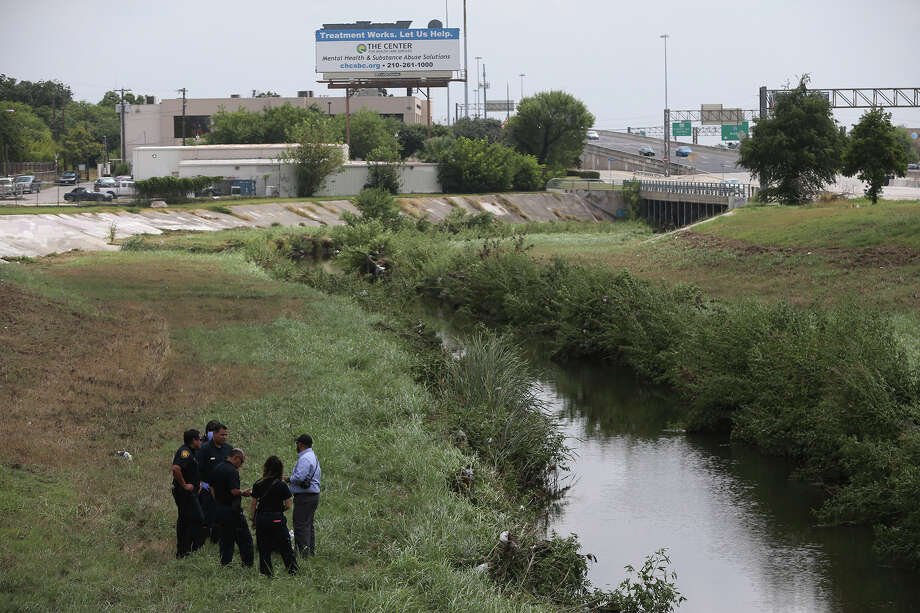 Police and fire personnel stand next to the bank of a creek Friday September 11, 2015 near Fulton and Interstate 10 where the body of a man was found after being swept away during yesterday's rain storm. Photo: John Davenport, San Antonio Express-News / ©San Antonio Express-News/John Davenport