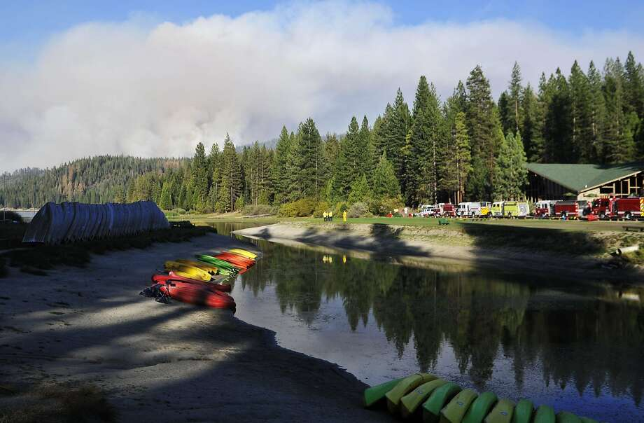 In this Aug. 19, 2015 photo, boats are beached and fire personnel staff Hume Lake in the Sequoia National Forest as the Rough fire continues burning in the background. California's largest wildfire burning near the popular Hume Lake in the Central Sierra Nevada is expected to rage through the holiday weekend, and the forestry officials encourage campers to set up their tents elsewhere. (Eric Paul Zamora/The Fresno Bee via AP) Photo: Eric Paul Zamora, Associated Press