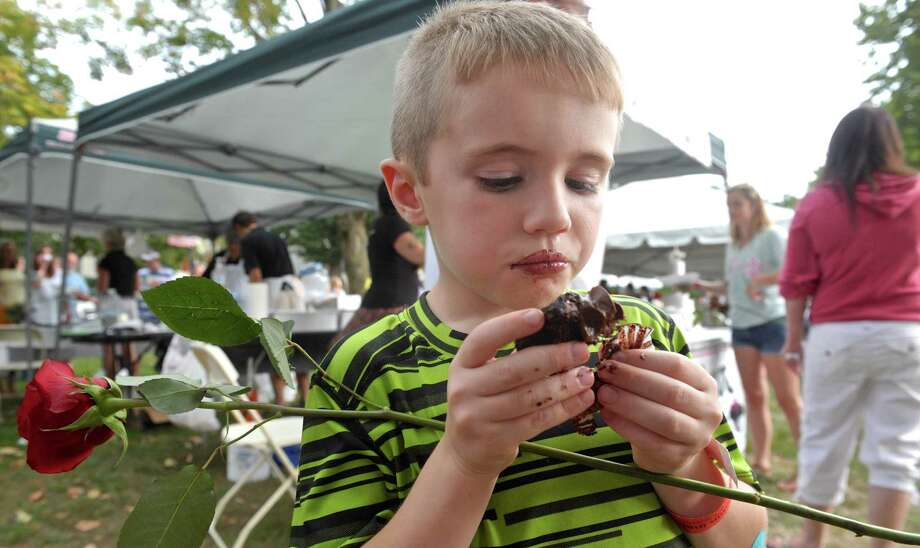 James Tong, 6, of New Milford, digs into a chocolate cupcake from The Sweet Spot, at the 10th annual Taste of New Milford on the Village Green Wednesday night. Photo: H John Voorhees III / Hearst Connecticut Media / The News-Times