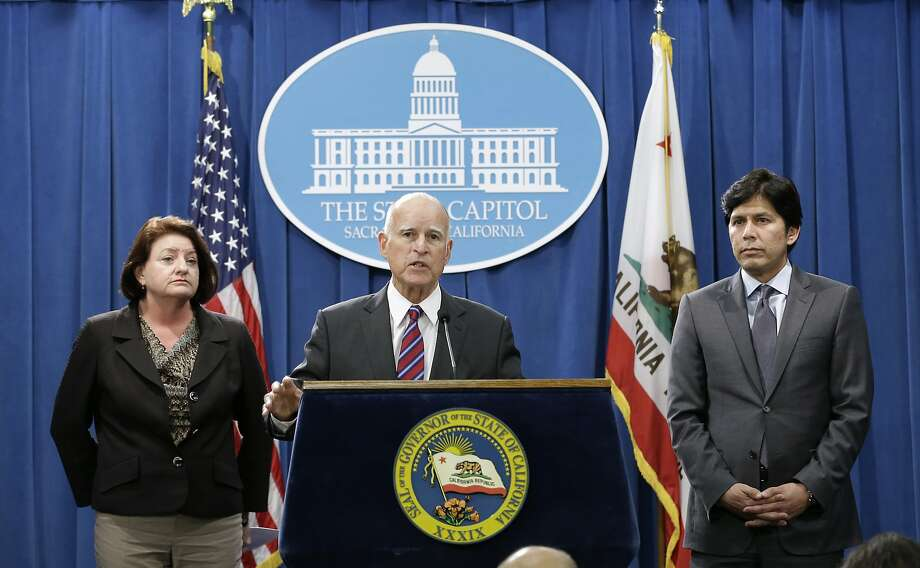 Gov. Jerry Brown, flanked by outgoing Assembly Speaker Toni Atkins, D-San Diego, and state Senate President Pro Tem Kevin de León, D- Los Angeles, announces his plan to scale back their climate change proposal Wednesday at the state Capitol. Photo: Rich Pedroncelli, Associated Press