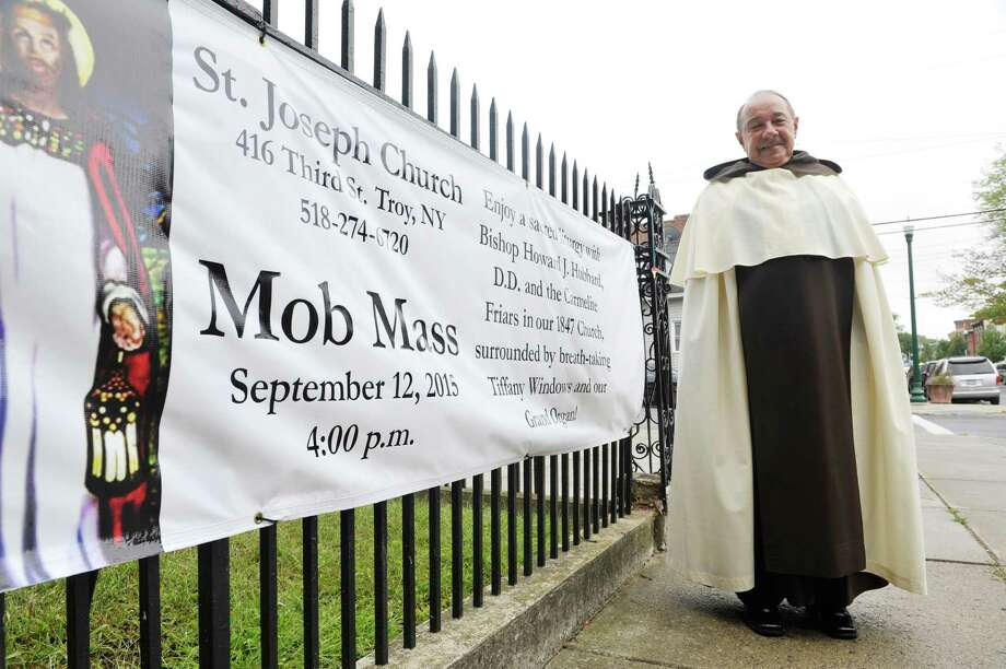 Pastor of Church of St. Joseph, Rev. James R. Sidoti, O. Carm., poses for a photograph by a banner for the Mass Mob at the Church of St. Joseph, on Thursday, Sept. 10, 2015, in Troy, N.Y.  (Paul Buckowski / Times Union) Photo: PAUL BUCKOWSKI / 00033279A