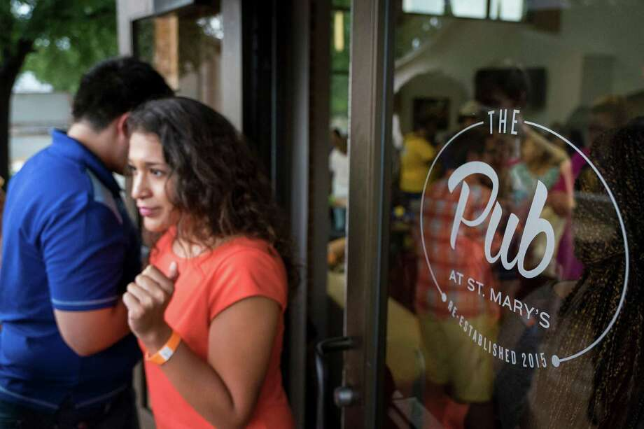 St. Mary's alumna Erika Renteria walks out of the Pub at St. Mary's during an event to commemorate its grand reopening on Thursday. Photo: Darren Abate /For The San Antonio Express-News