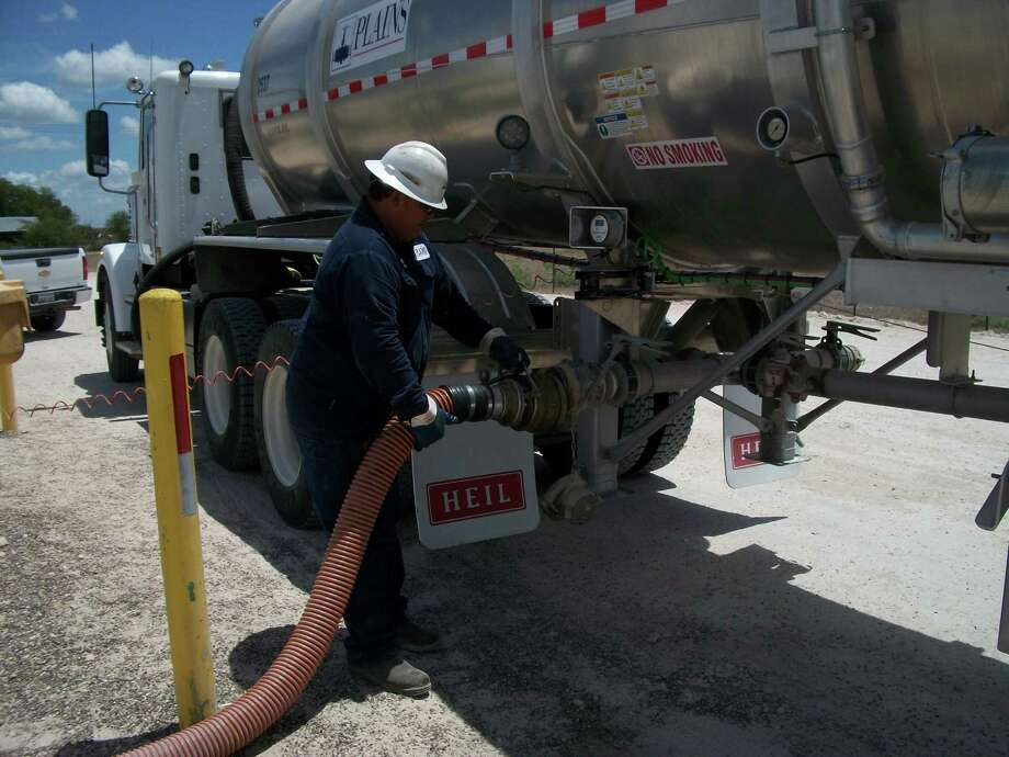 A Plains All American driver disconnects a hose after unloading Eagle Ford crude oil into a Plains South Texas truck station. Photo: Plains All American / Plains All American Pipeline