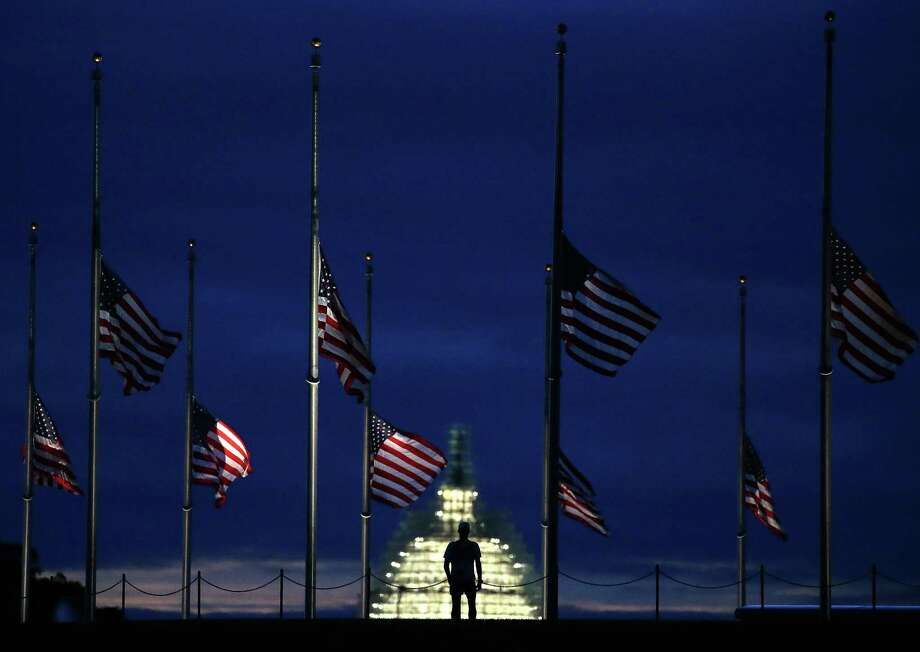 WASHINGTON, DC - SEPTEMBER 11: A man walks past a row of American flags that have been lowered to half staff on the Washington Monument grounds, near the US Capitol on September 11, 2015 in Washington, DC. Today marks the fourteenth anniversary of the September 11, 2001 attacks when terroristists high jacked airliners and flew them in the World Trade Center and the Pentagon. (Photo by Mark Wilson/Getty Images) Photo: Mark Wilson, Staff / Getty Images / 2015 Getty Images