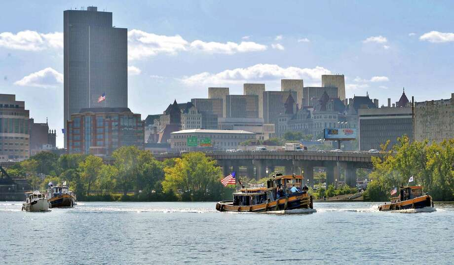 Canal Corporation's flagship tugs, URGER Urger, Grand Erie, and Tender 3 lead the 16th annual Waterford Tugboat Roundup past the Albany skyline Friday Sept. 11, 2015, as seen from the boat launch in Rensselaer, NY.    (John Carl D'Annibale / Times Union) Photo: John Carl D'Annibale / 00033315A