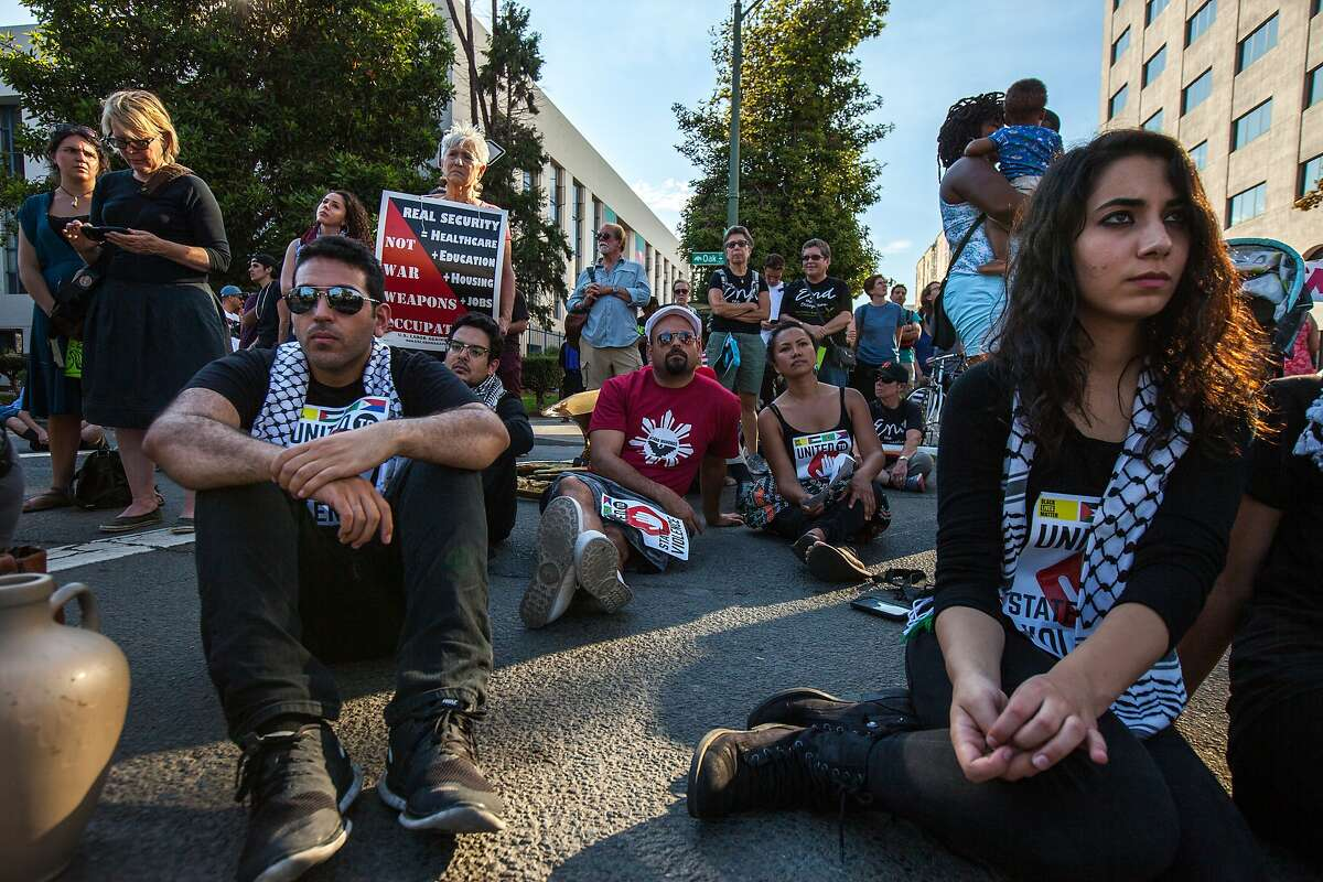 Siraj Al-Kateb (left) and Subhiyeh Aantar, both of the Palestinian Youth Movement from Los Angeles, listen in to the speaker during a demonstration against the Urban Shield convention, Friday, Sept. 11, 2015, at the intersection of 14th Street and Lakeside Drive in Oakland, Calif. The convention, which critics say increases the militarization of police, moved to a different venue after last year's event was the scene of large protests. Urban Shields presents training exercises to first responders.