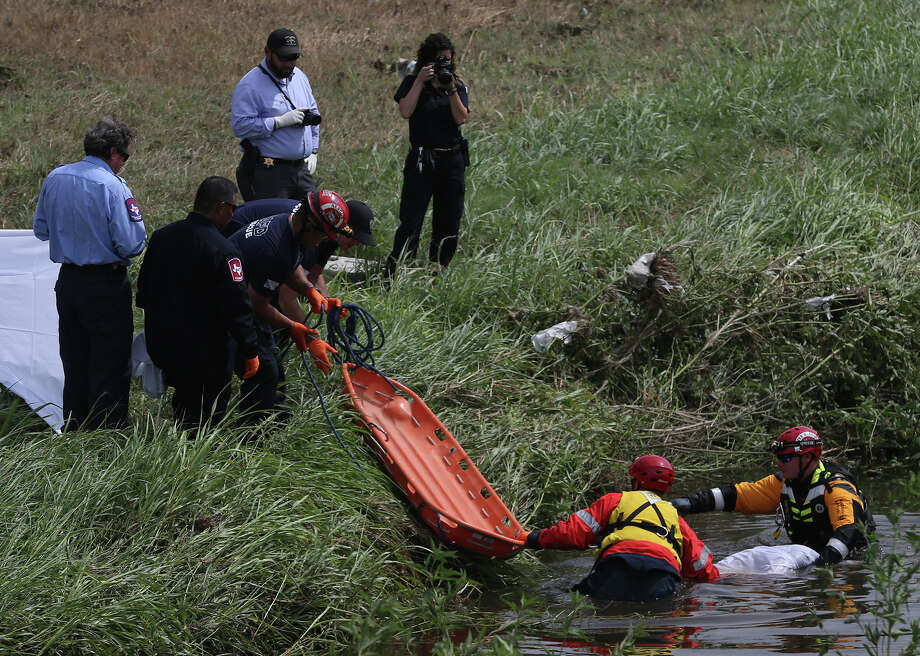 Police and fire personnel prepare to remove a body from a creek near Interstate 10 and Fulton Avenue, about 2 miles from where a man was swept away by rising water during the thunderstorm on Thursday. Friday September 11, 2015 near Fulton and Interstate 10 where the body of a man was found after being swept away during yesterday's rain storm. Photo: John Davenport /San Antonio Express-News / ©San Antonio Express-News/John Davenport