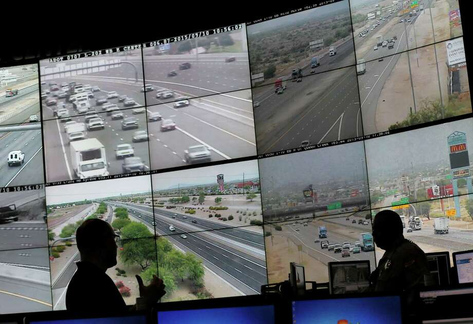 Arizona Department of Transportation Live Traffic Operations operators monitor more than 200 freeway cameras throughout the Phoenix area on Thursday. Police detained a man Friday who a spokesman said is of interest to investigators in the case. Photo: Matt York, STF / ap